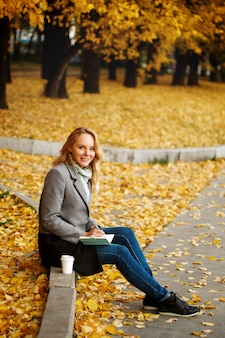 Woman sitting on a curb writing something in her notebook autumn nature with golden trees around