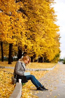 Woman sitting on a curb and writing something in her notebook in autumn park with golden trees