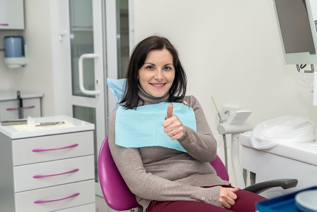 Woman sitting in dentist chair showing thumb up