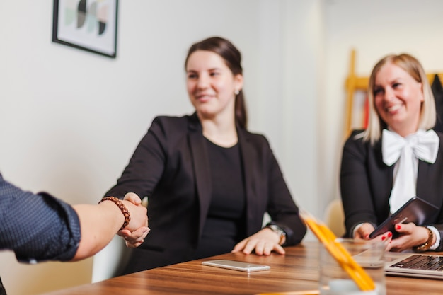 Woman sitting at desk shaking mans hand