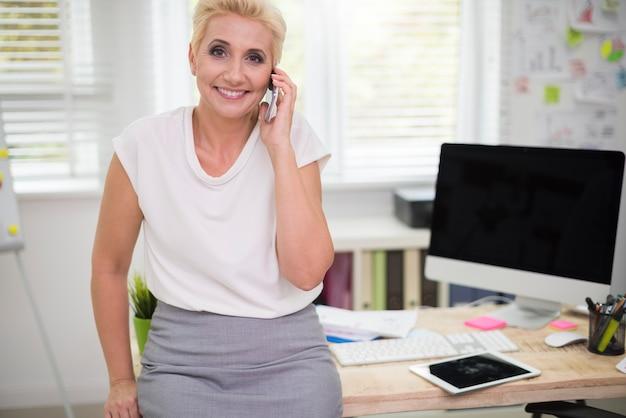 Donna seduta sulla scrivania e parlando al telefono