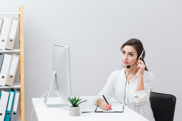 Woman sitting at desk and writing something down while listening on headset