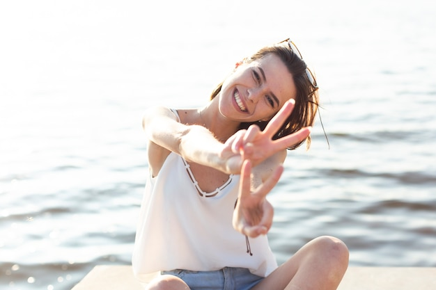Woman sitting on dock doing the peace sign