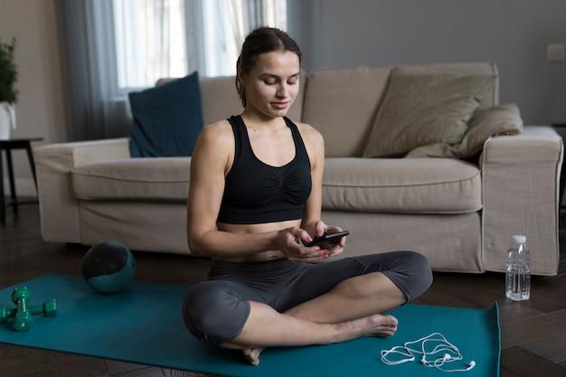 Женщина сидит на коврик для йоги и с помощью смартфона