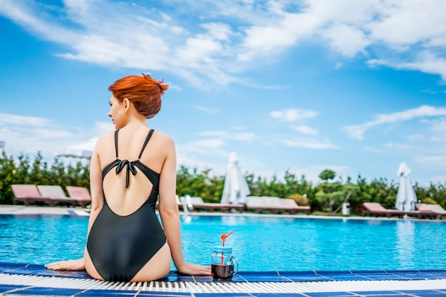 Woman sitting on the edge of the swimming pool with smoothie mason jar in a tropical hotel