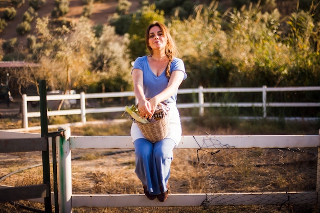Woman sitting on the fence holding basket of harvested vegetable