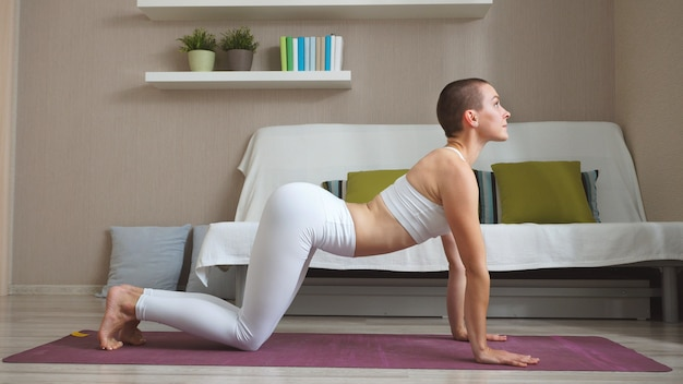 Woman sitting on a fitness. mat at home doing yoga, cat pose