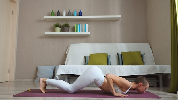 Woman sitting on a fitness mat at home doing yoga, cat pose