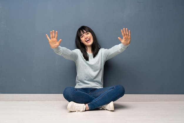 Woman sitting on the floor counting ten with fingers