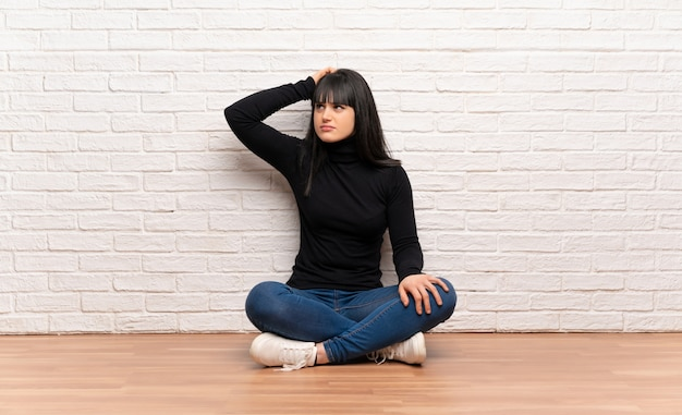Woman sitting on the floor having doubts while scratching head
