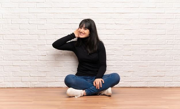 Woman sitting on the floor listening to something by putting hand on the ear