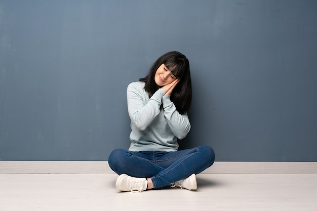 Woman sitting on the floor making sleep gesture in dorable expression