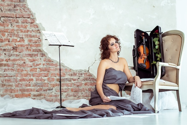 Woman sitting on the floor near the chair with violin