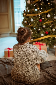 Woman sitting on floor near christmas tree