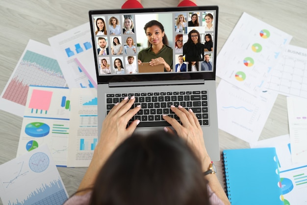 Woman sitting on floor near documents and communicating via video link with team of employees top view