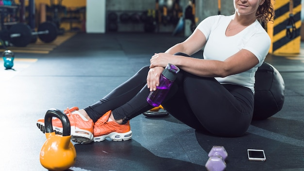 Woman sitting on floor near exercise equipments and cellphone in gym
