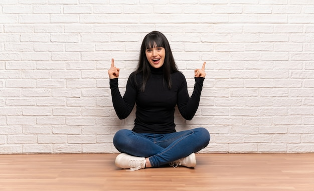 Woman sitting on the floor pointing with the index finger a great idea