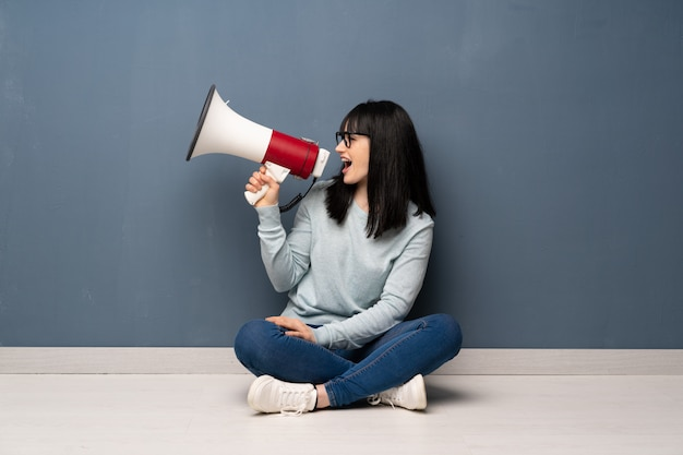 Woman sitting on the floor shouting through a megaphone