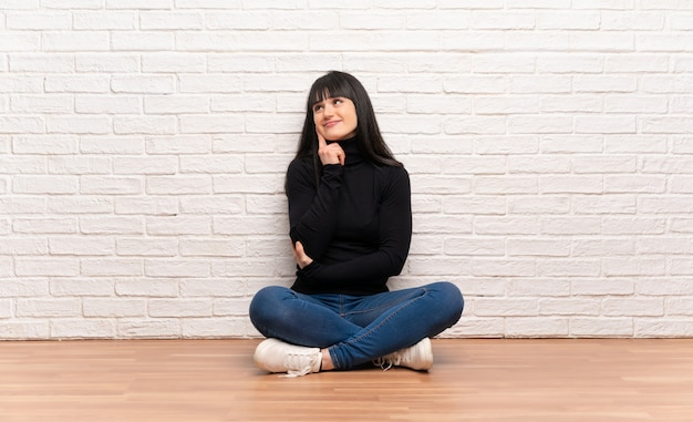 Woman sitting on the floor thinking an idea while looking up