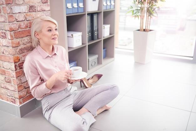 Donna seduta sul pavimento con una tazza di caffè in ufficio