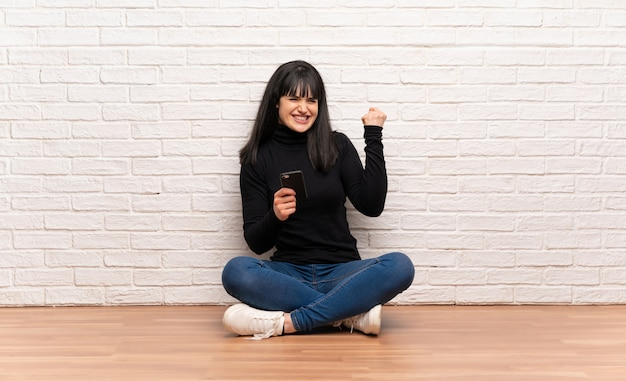 Woman sitting on the floor with phone in victory position