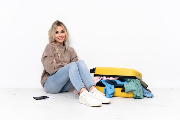 Woman sitting on the floor with suitcase over isolated wall