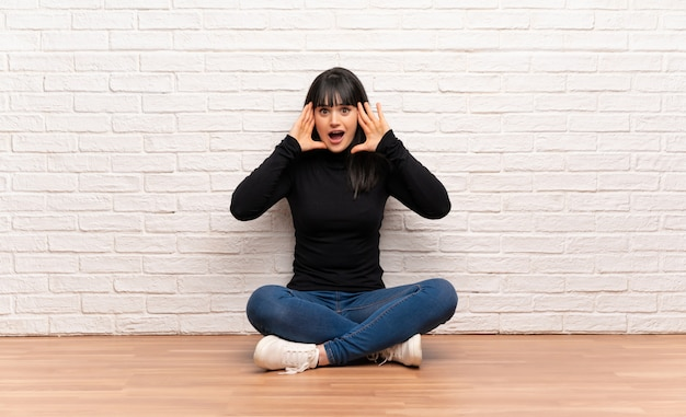 Woman sitting on the floor with surprise expression