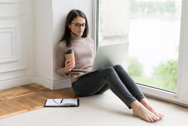Donna seduta sul pavimento che lavora al suo laptop