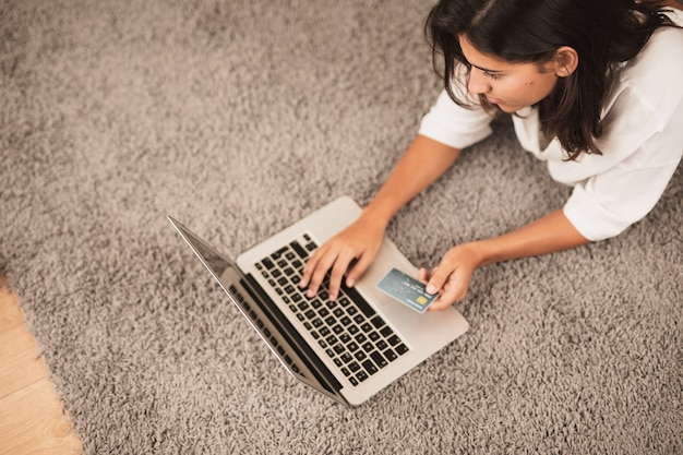 Woman sitting on floor and working on laptop