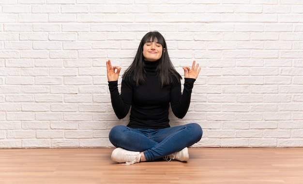 Woman sitting on the floor in zen pose