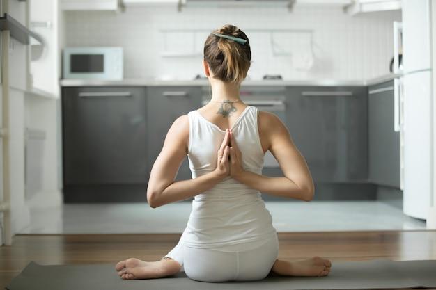 Woman sitting in gomukasana pose