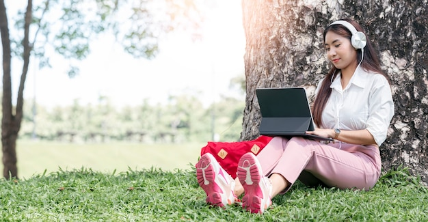Woman sitting on grass under big tree at park working on laptop. young woman wearing earphones using laptop while sitting under a tree at park with bright sunlight from behind.