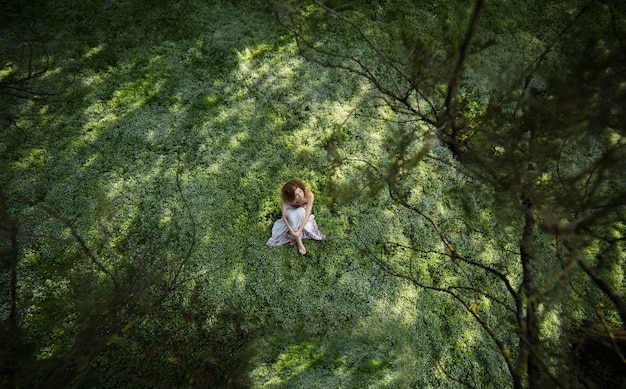Woman sitting on the grass viewed from above