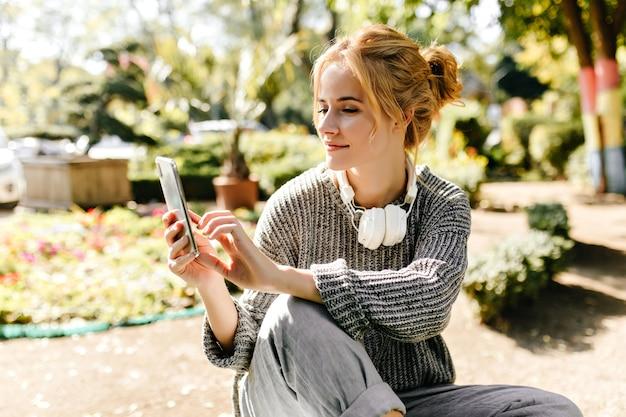 Donna seduta in serra prende selfie sul suo telefono