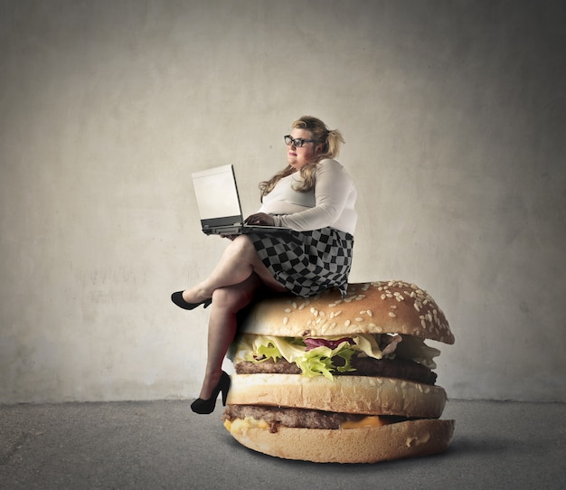 Woman sitting on a hamburger
