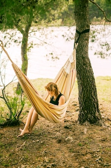 Woman sitting in hammock on riverbank