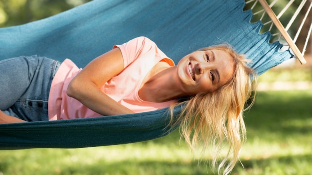 Woman sitting in hammock and smiles