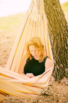 Woman sitting in hammock with smartphone