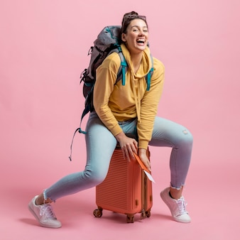 Woman sitting on her baggage while laughing