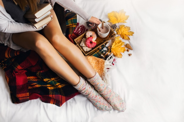 Woman sitting in her bed with books and drinking coffee with cinnamon, cookies and glazed donuts.
