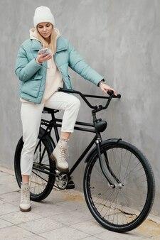 Donna seduta sulla sua bici e utilizzando il suo telefono cellulare