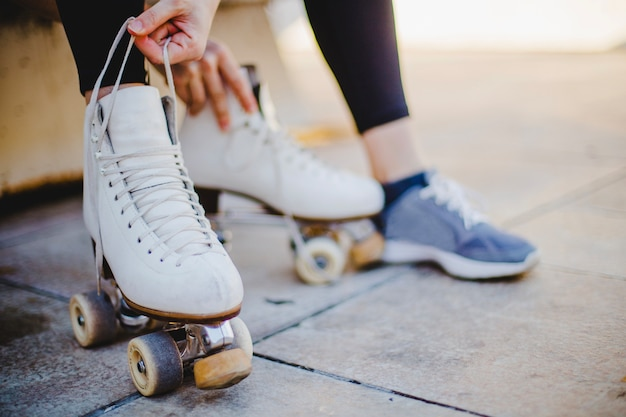 Woman sitting holding laces of roller skates