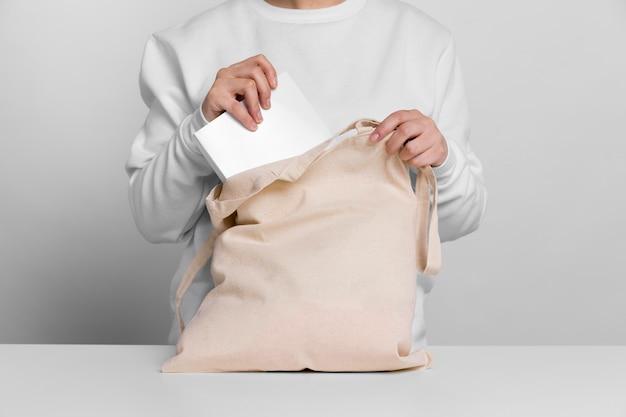 Donna seduta e tenendo una tote bag sul tavolo