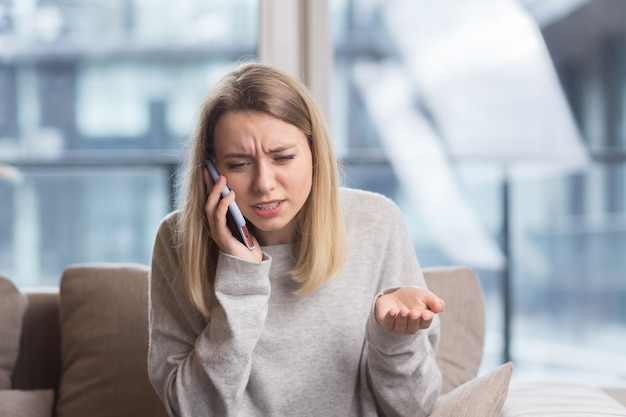 Woman sitting at home on the couch with a severe headache trying to call a doctor with a phone