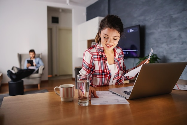 Woman sitting at home and looking at laptop. her husband standing behind her and looking at laptop