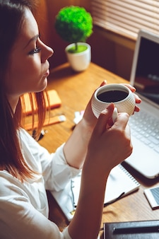 Woman sitting at home office with cup of coffee