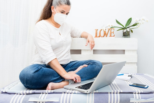 Woman sitting on home sofa using laptop with antivirus mask