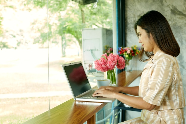 Woman sitting at home using laptop