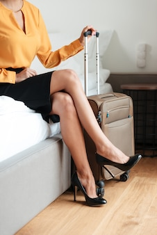Woman sitting on hotel bed next to her suitcase