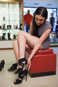 Женщина, сидящая в бутике, пытаящая обувь